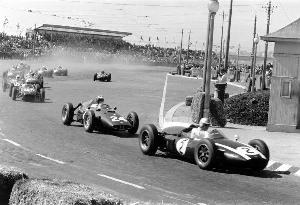 1960 Portuguese Grand Prix.Oporto, Portugal. 14 August 1960.Jack Brabham, Cooper T53-Climax, 1st position, leads Dan Gurney, BRM P48, retired, John Surtees, Lotus 18-Climax, retired, and Stirling Moss, Lotus 18-Climax, disqualified, into the Avenida Da Boavista at the start, action.World Copyright: LAT PhotographicRef: Autosport b&w print. Published: Autosport, 19/8/1960 p257