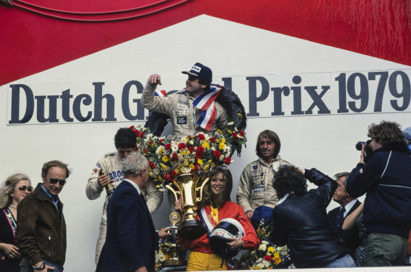 Alan Jones celebrates victory on the podium with Jody Scheckter, 2nd position, and Jacques Laffite, 3rd position.