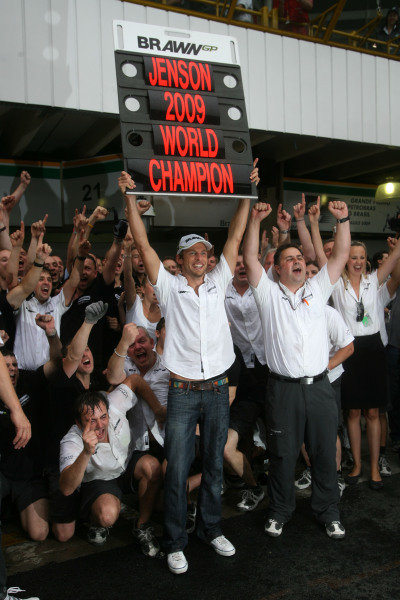 Jenson Button celebrates his drivers' world championship title with his team in the pit lane.