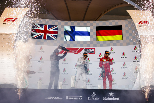 Lewis Hamilton, Mercedes AMG F1, 2nd position, Valtteri Bottas, Mercedes AMG F1, 1st position, and Sebastian Vettel, Ferrari, 3rd position, celebrate amid fireworks on the podium
