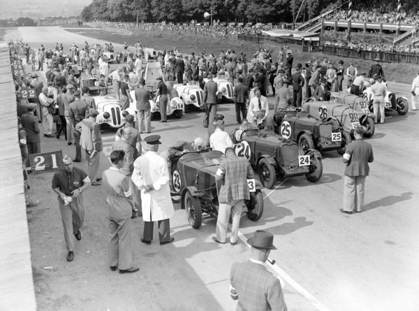 A crowd gathers on the grid as the cars prepare for the start of the race.