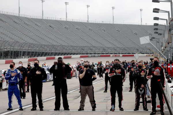 Teams stand on pit road during the national anthem, Copyright: Chris Graythen/Getty Images.