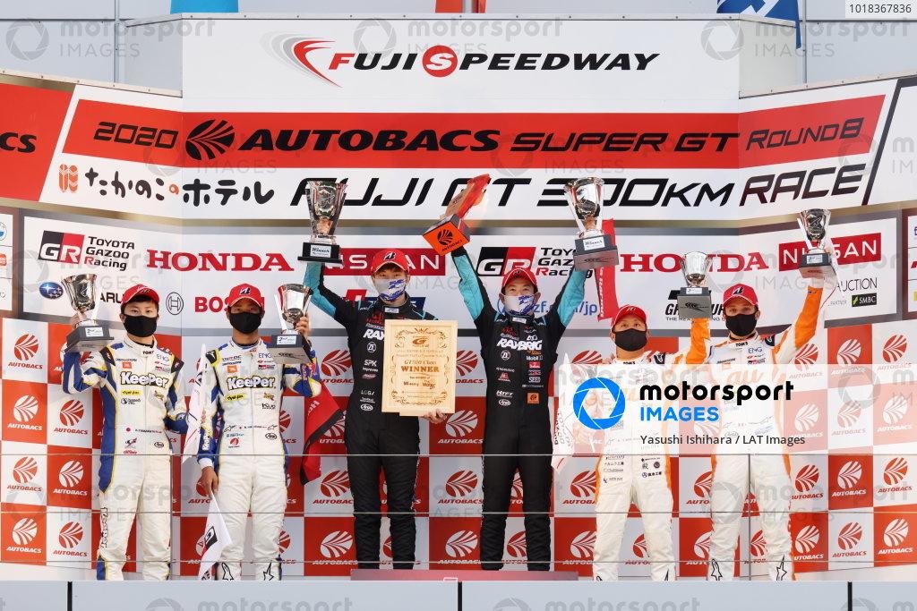 GT500 Winners and 2020 GT500 Drivers' Champions Naoki Yamamoto & Tadasuke Makino ( #100 RAYBRIG Honda NSX-GT ) celebrate on the podium. Either side are Ryo Hirakawa & Kenta Yamashita ( #37 KeePer TOM'S Toyota GR Supra ) 2nd position, and Yuhi Sekiguchi & Sacha Fenestraz ( #36 au TOM'S Toyota GR Supra ) 3rd position