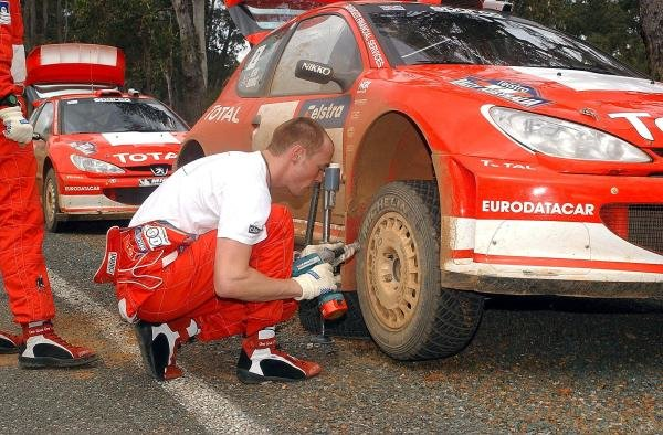 Richard Burns (GBR) Peugeot changes a wheel between stages.