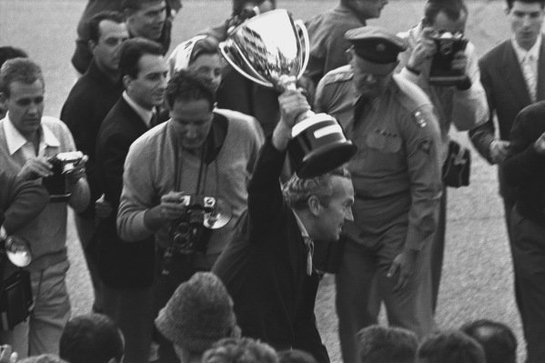 Monza, Italy. 6th - 8th September 1963.  Jim Clark (Lotus 25 Climax) gives team boss Colin Chapman a lift, as they celebrate finishing in 1st position and clinching the drivers and constructors World Championship titles, portrait. World Copyright: LAT Photographic. Reff: L63 - 282 - 34.