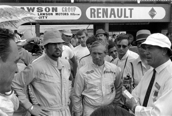 Jo Bonnier (SWE), left, Mike Spence (GBR), centre, and Dan Gurney (USA), Eagle, far left, listen to an announcement from a race official. South African Grand Prix, Rd1, Kyalami, South Africa, 1 January 1968.