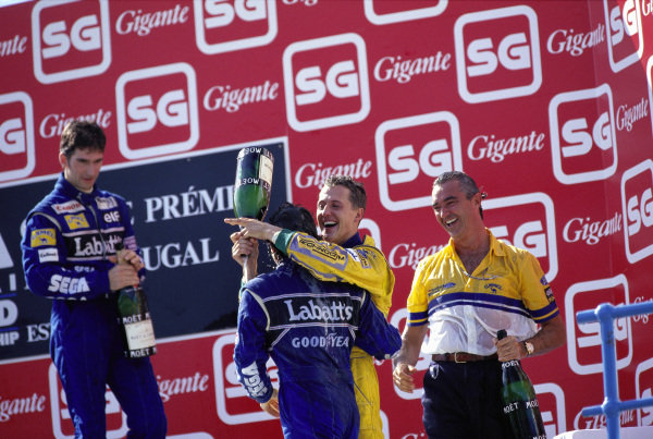 Michael Schumacher, 1st position, celebrates on the podium with Alain Prost, 2nd position  Damon Hill, 3rd position, and Flavio Briatore.