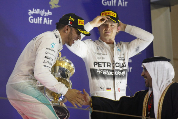 Lewis Hamilton, 1st position, receiving the winners trophy from Crown Prince Shaikh Salman bin Hamad Al Khalifa with Nico Rosberg, 3rd position, in the background.
