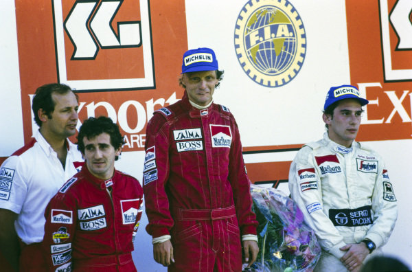 Niki Lauda, 2nd position, stands on top of the podium as the newly-crowned world champion. Alongside him are Alain Prost, 1st position, Ayrton Senna, 3rd position, and Ron Dennis.