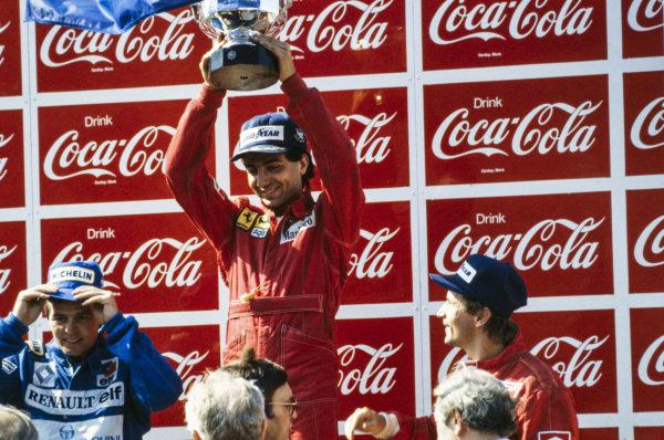 Michele Alboreto, 1st position, raises his trophy alongside Derek Warwick, 2nd position, and René Arnoux, 3rd position.