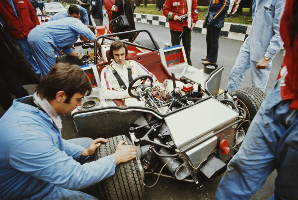 Tim Schenken sits aboard the Ferrari SpA SEFAC, Ferrari 312 PB as mechanics make adjustments to the front end in the pitlane.