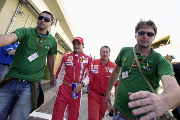 Bodyguards escort pole sitter Felipe Massa to the press conference.