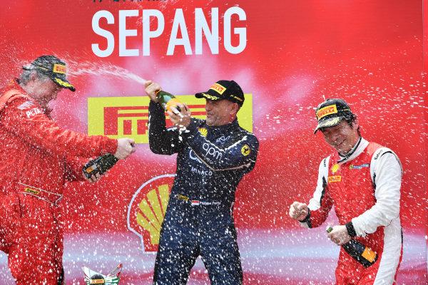 Philippe Prette, Blackbird Concessionaires HK, celebrates victory with champagne alongside James Weiland, Ferrari of Cincinnati, and Nobuhiro Imada, Rosso Scuderia on the podium