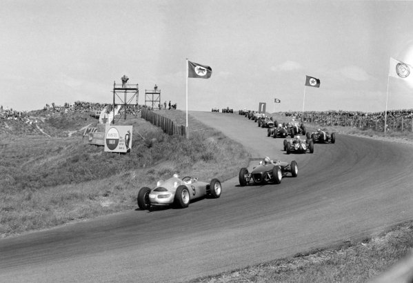 1961 Dutch Grand Prix Zandvoort, Holland. 20-22 May 1961 Hans Herrmann (#9 Porsche 718) follows the field after the start. In the distance Wolfgang von Trips (Ferrari Dino 156) leads Graham Hill (BRM P48/57-Climax), Phil Hill (Ferrari Dino 156), Jim Clark (Lotus 21-Climax), Dan Gurney (Porsche 787), Stirling Moss (Lotus 18-Climax), Richie Ginther (Ferrari Dino 156), Jo Bonnier (Porsche 787), Jack Brabham (Cooper T55-Climax), Tony Brooks (BRM P48/57-Climax), Bruce McLaren (Cooper T55-Climax), John Surtees (#12 Cooper T53-Climax), Trevor Taylor (Lotus 18-Climax) and Herrmann World Copyright: LAT PhotographicRef: Autosport b&w print
