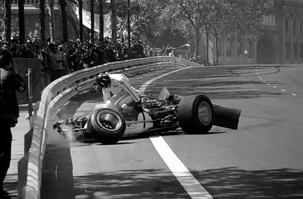 Graham Hill (GBR) climbs from the wreckage of his Lotus 49B, his rear wing having collapsed on the ninth lap. The accident illustrated the worthiness of Armco barriers and the inherent dangers of movable high aerofoils, which were banned shortly thereafter.   Spanish Grand Prix, Montjuich Park, 4 May 1969.