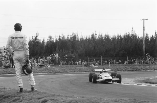 1969 Mexican Grand Prix.Mexico City. 19 October 1969.Having retired from the race, Jo Siffert watches Denny Hulme (McLaren M7A-Ford Cosworth), 1st position. Ref-2767 #16A.World Copyright - LAT Photographic
