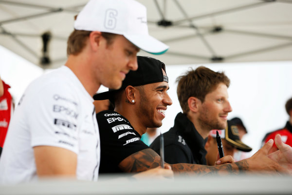 Hungaroring, Budapest, Hungary. Thursday 23 July 2015. Nico Rosberg, Mercedes AMG, Lewis Hamilton, Mercedes AMG, and Romain Grosjean, Lotus F1, sign autographs for fans. World Copyright: Charles Coates/LAT Photographic ref: Digital Image _J5R0496