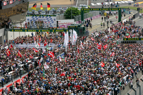 Circuit de La Sarthe, Le Mans, France. 6th - 13th June 2010.A huge crowd forms beneath the podium to celebrate a clean sweep for Audi with Mike Rockenfeller / Timo Bernhard / Romain Dumas, Audi Sport North America, No 9 Audi R15-Plus TDI, 1st position, Andre Lotterer / Marcel Fassler / Benoit Treluyer, Audi Sport Team Joest, No 8 Audi R15-Plus TDI, 2nd position, and Tom Kristensen / Dindo Capello / Allan McNish, Audi Sport Team Joest, No 7 Audi R15-Plus TDI, 3rd position. Portrait. Podium.World Copyright: Alastair Staley/LAT PhotographicDigital Image _P9O8991 jpg