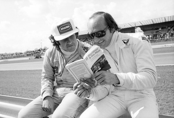 (L to R): Carlos Pace (BRA) Surtees enjoys reading 'Machines & The Men,' a book by Andrew Marriott and Anna O'Brien, with Mike Hailwood (GBR) McLaren.Belgian Grand Prix, Rd 5, Nivelles-Baulers, Belgium, 12 May 1974.