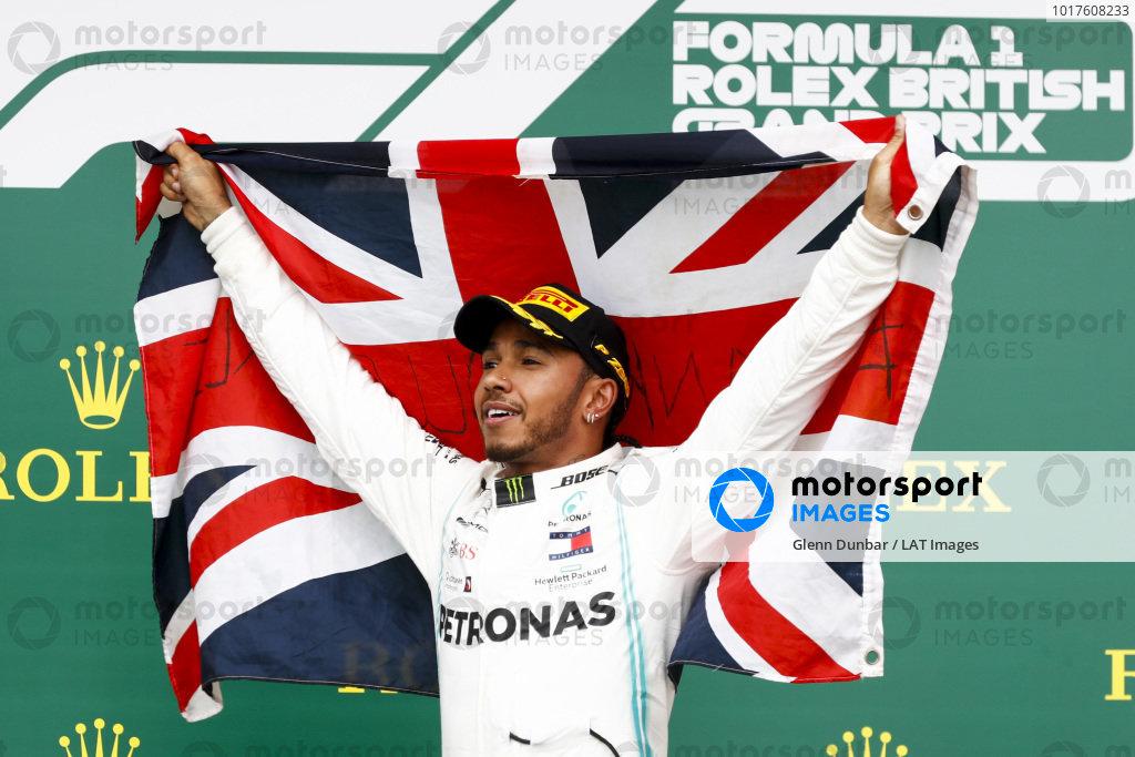 Race winner Lewis Hamilton, Mercedes AMG F1 celebrates on the podium with a flag