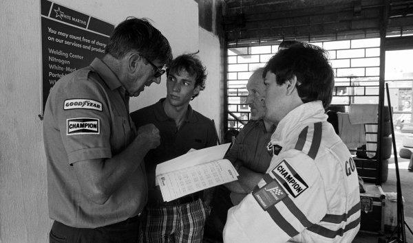 (L to R): Ken Tyrrell (GBR) Team Owner chats to Stefan Bellof (GER) and Martin Brundle (GBR) Tyrrell.Formula One World Championship, Rd 1, Brazilian Grand Prix, Rio de Janeiro, Brazil, 25 March 1984.