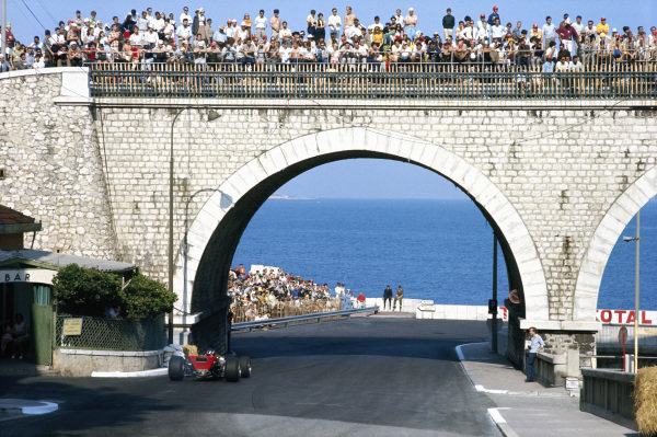 Graham Hill, Lotus 49B Ford, drives under a bridge full of spectators.