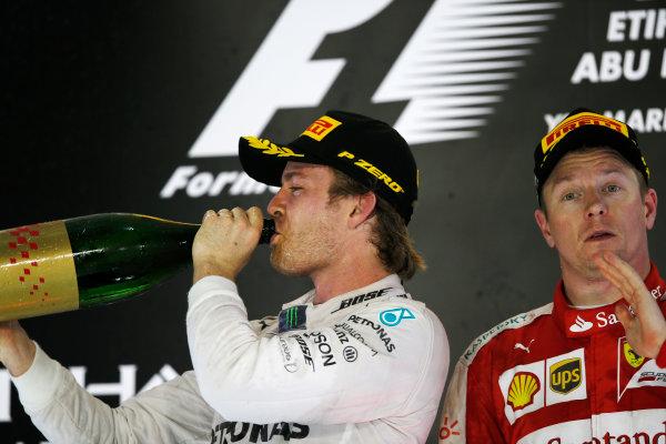 Yas Marina Circuit, Abu Dhabi, United Arab Emirates. Sunday 29 November 2015. Nico Rosberg, Mercedes AMG, 1st Position, and Kimi Raikkonen, Ferrari, 3rd Position, celebrate on the podium. World Copyright: Charles Coates/LAT Photographic ref: Digital Image _99O2744