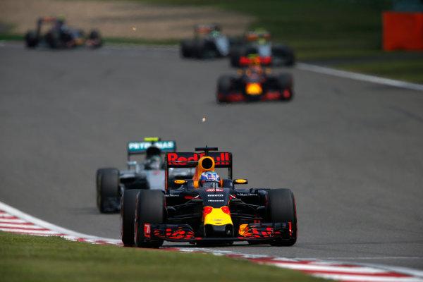Shanghai International Circuit, Shanghai, China. Sunday 17 April 2016. Daniel Ricciardo, Red Bull Racing RB12 TAG Heuer leads Nico Rosberg, Mercedes F1 W07 Hybrid on the first lap of the race. World Copyright: Glenn Dunbar/LAT Photographic ref: Digital Image _89P3779