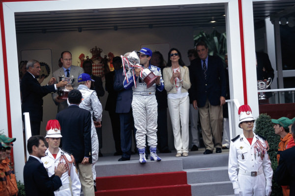 Juan Pablo Montoya, 1st position kissing his trophy on the podium. Kimi Räikkönen, 2nd position, prepares to receive his trophy from Prince Albert.