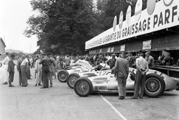 The Mercedes-Benz W154s lined up in the pits, with Hermann Lang's (#14) nearest the camera.  The car of Walter Bäumer (#11) that was only used in practice, can just be seen halfway along.