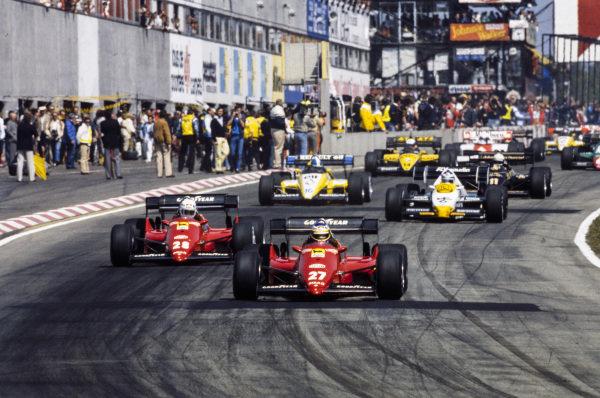 Michele Alboreto, Ferrari 126C4, leads René Arnoux, Ferrari 126C4, Keke Rosberg, Williams FW09 Honda, Derek Warwick, Renault RE50, Elio de Angelis, Lotus 95T Renault, and Manfred Winkelhock, ATS D7 BMW, at the start.
