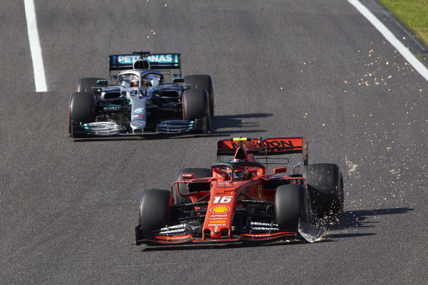 Charles Leclerc, Ferrari SF90, drags a sparking front wing endplate, ahead of Lewis Hamilton, Mercedes AMG F1 W10