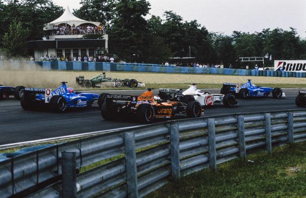 Eddie Irvine, Jaguar R2 Cosworth, runs wide at the first corner. Meanwhile, Giancarlo Fisichella, Benetton B201 Renault, leads Olivier Panis, BAR 003 Honda, Jos Verstappen, Arrows A22 Asiatech, and Jenson Button, Benetton B201 Renault.