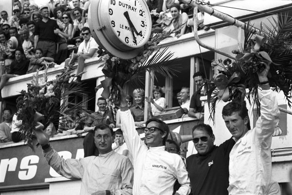 Overall winners Masten Gregory and Jochen Rindt (in white) celebrate on the podium with class winners Peter Noecker and Herbert Linge.