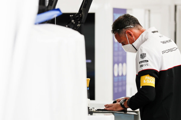 A member of the Andre Lotterer Tag Heuer Porsche team at work in the garage