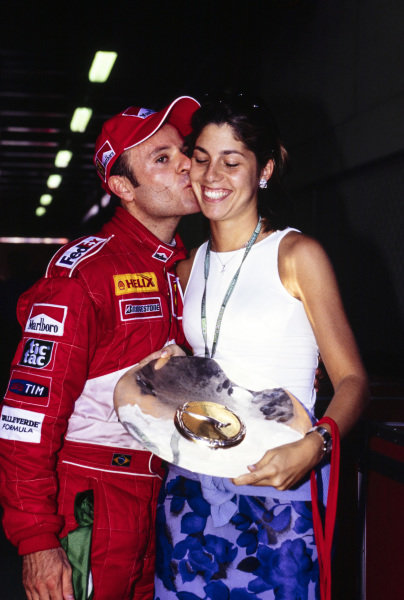 Rubens Barrichello kisses his wife, Silvana, while she holds his trophy for second place.