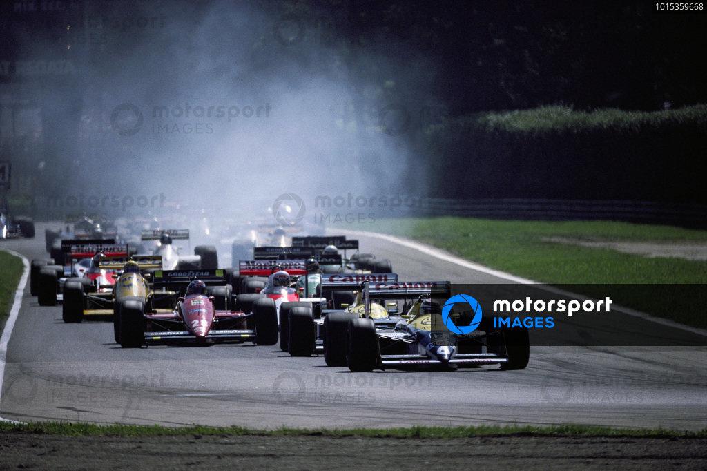 Nelson Piquet, Williams FW11B Honda, leads teammate Nigel Mansell and Gerhard Berger, Ferrari F1-87, at the start.