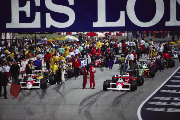 Alain Prost and Ayrton Senna talk on the grid before the restart, with the race red flagged due to Gerhard Berger's crash.