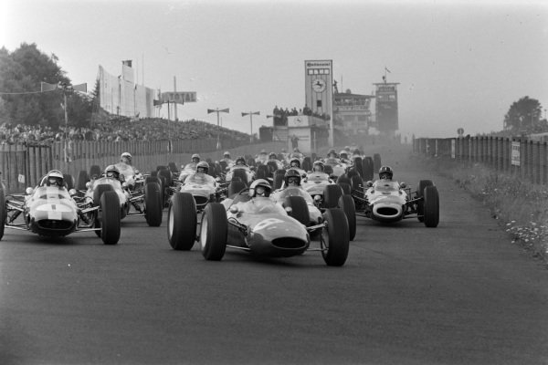 Lorenzo Bandini, Ferrari 156 Aero, leads Jim Clark, Lotus 33 Climax, Dan Gurney, Brabham BT7 Climax, Graham Hill, BRM P261, Jack Brabham, Brabham BT7 Climax, and the rest of the field at the start of the race.