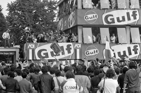 Clay Regazzoni, 1st position, stands on the crowded podium as fans look on.