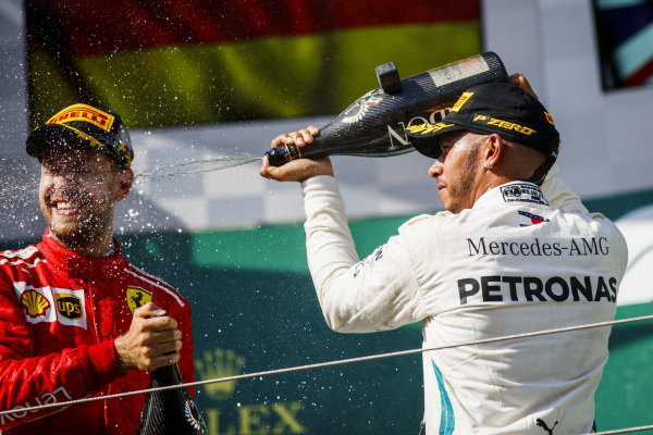 Sebastian Vettel, Ferrari celebrates by spraying champagne on the podium with Lewis Hamilton, Mercedes AMG F1.