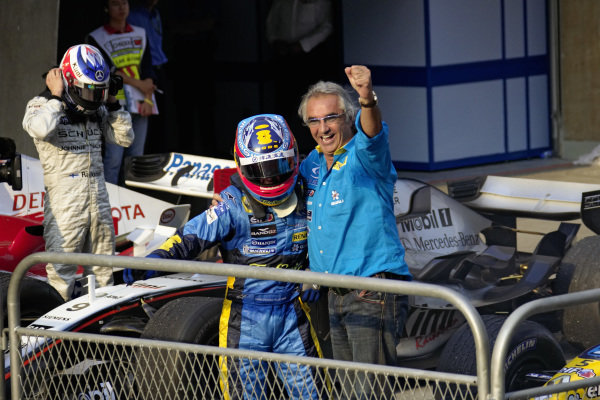 Fernando Alonso celebrates victory and clinching the constructors' championship with Flavio Briatore in parc ferme.