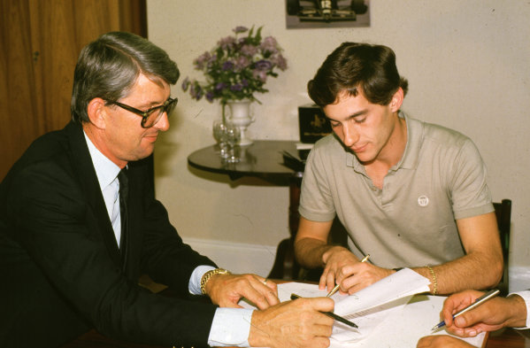 1985 Formula 1 World Championship.Ayrton Senna signs for Lotus-Renault in the presense of team manager Peter Warr (left).Ref-S1C 05.World - LAT Photographic
