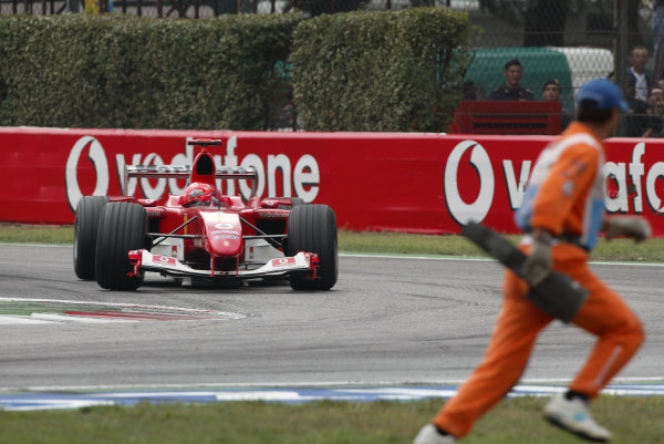 2004 Italian Grand Prix - Sunday Race,Monza, Italy. 12th September 2004 A marshal removes a piece of debris, as Michael Schumacher, Ferrari F2004, passes. Action.World Copyright: Steve Etherington/LAT Photographic ref: Digital Image Only