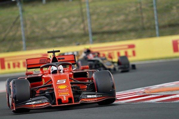 Sebastian Vettel, Ferrari SF90 and Kevin Magnussen, Haas VF-19