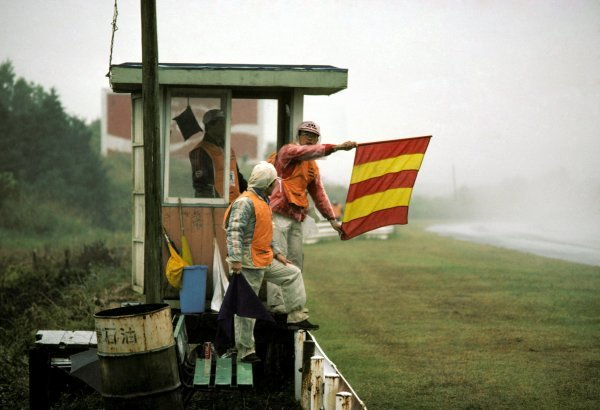 A trackside marshal holds out the red and yellow striped flag, warning drivers that there was water on the track. The race was nearly cancelled because of the appalling wet conditions. Japanese Grand Prix, Rd 16, Fuji, Japan, 24 October 1976. BEST IMAGE