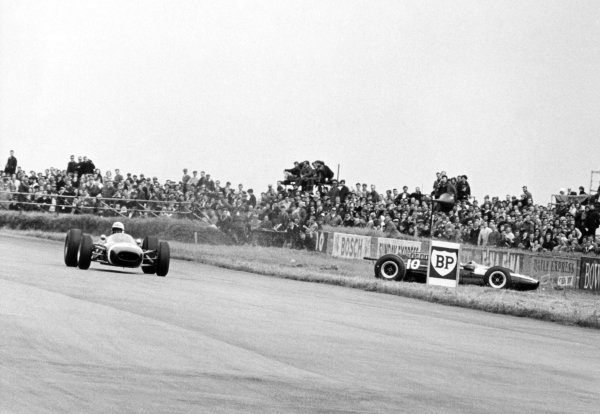 1965 British Grand Prix.Silverstone, Great Britain. 10 July 1965.Jo Bonnier, Brabham BT7-Climax, 7th position, passes as Jochen Rindt, Cooper T77-Climax, 14th position, spins at Becketts, action.World Copyright: LAT Photographic