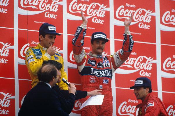 Imola, Italy. 1-3 May 1987. Nigel Mansell (Williams Honda) 1st position, Ayrton Senna (Lotus Honda) 2nd position, and Michele Alboreto (Ferrari) 3rd position, on the podium.Ref-87 SM 07. World Copyright - LAT Photographic