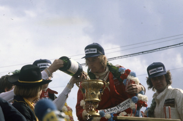 James Hunt celebrates victory on the podium, watching as his trophy is filled with champagne with Niki Lauda, 2nd position, and Gunnar Nilsson, 3rd position.