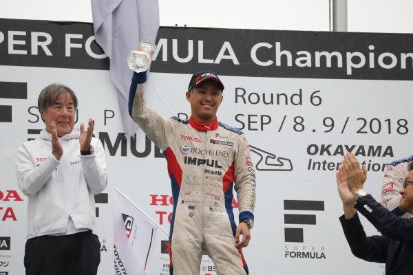 Winner Yuhi Sekiguchi, Itochu Enex Team Impul SF14 Toyota, celebrates on the podium, as team boss Kazuyoshi Hoshino applauds.